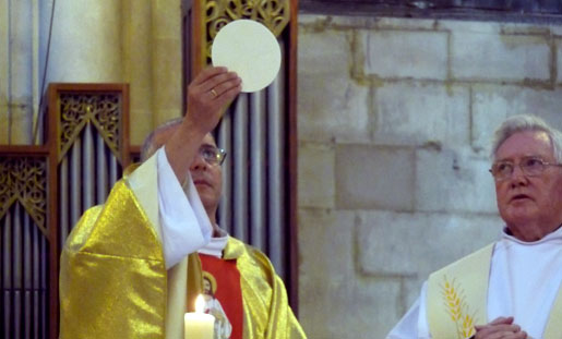 Priest holds Eucharist towards Heaven